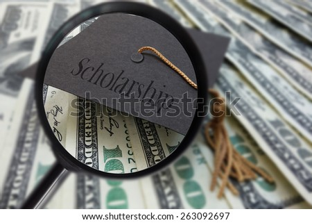 Magnified graduation mortar board with Scholarship text, on money                                - stock photo