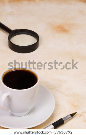 magnifier and cup of coffee at texture - stock photo