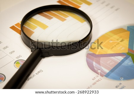 Magnifier and graphs analysis on table. - stock photo