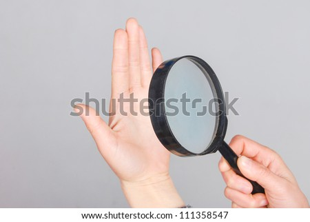 Magnifier and hand - stock photo