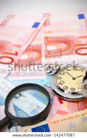 Magnifier and watch for euro. - stock photo