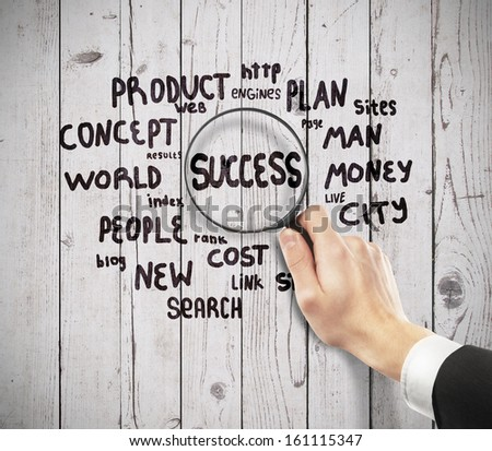 magnifier in hand looking at success - stock photo