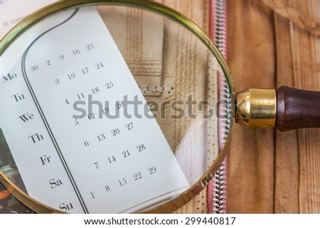 Magnifier Lying On The Calendar Close Up - stock photo