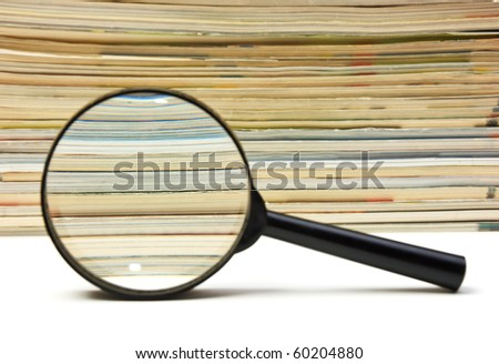 magnifier on the background of the stack of magazines - stock photo