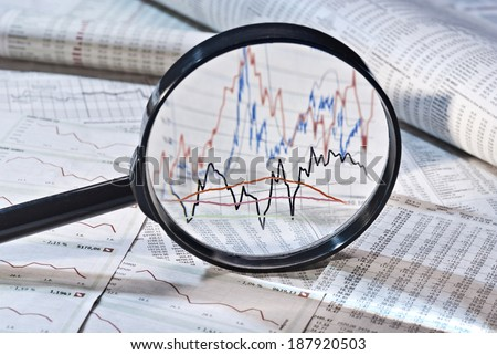 Magnifier shows the variation of stock prices, - stock photo