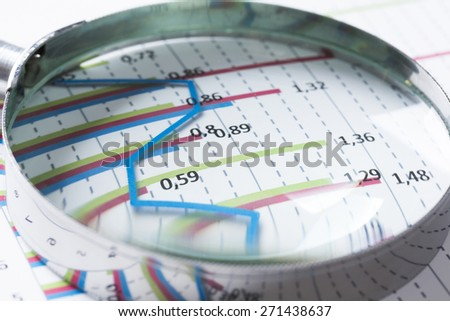 Magnifing glass and documents with analytics data lying on table  - stock photo