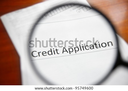 magnifying glass and a credit application form - stock photo