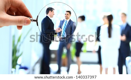 Magnifying glass and businessman in focus - stock photo