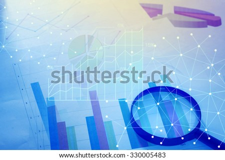 Magnifying glass and documents with analytics data lying on table - stock photo