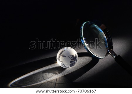 Magnifying glass and globe on dark background with beam of light - stock photo