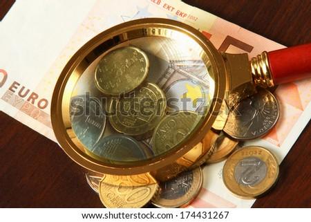 magnifying glass and money euro isolation on wood background - stock photo