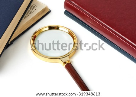 Magnifying glass and notebooks isolated on white background - stock photo