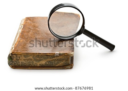 Magnifying glass and old book isolated on white - stock photo