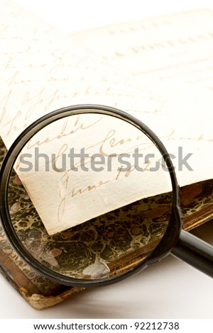 Magnifying glass and old book on the white background - stock photo