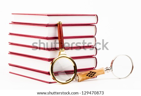 magnifying glass and pile of books isolated on white - stock photo