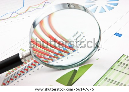 magnifying glass and the working paper with a diagram - stock photo