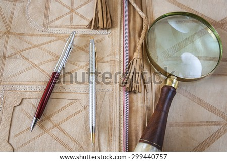 Magnifying Glass And Two Pens On Leather Folder - stock photo