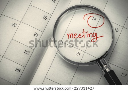 magnifying glass focus meeting date on dairy - stock photo