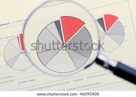 Magnifying glass focusing on a diagram - stock photo