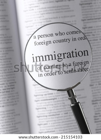 Magnifying Glass Highlighting Immigration - stock photo