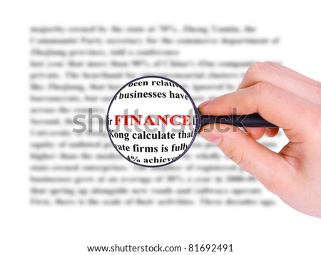 Magnifying glass in hand and word finance - stock photo
