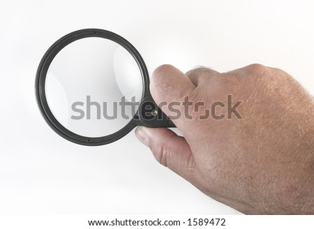 Magnifying glass in the hand - stock photo