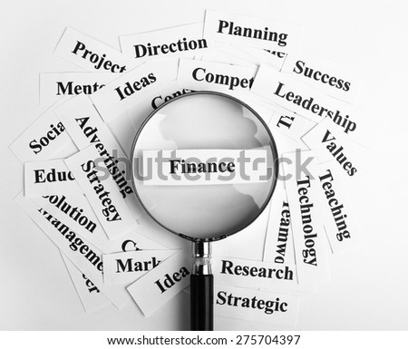 Magnifying glass is focusing on the finance word with lot of other business concept words around. - stock photo