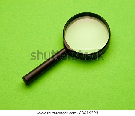 Magnifying glass isolated on the green background - stock photo