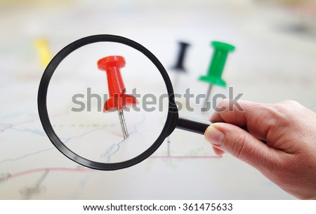 Magnifying glass looking at closeup of push pin tacks in a map                                - stock photo