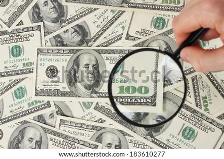 Magnifying glass on american hunderd dollars money - stock photo
