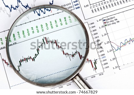 Magnifying glass on exchange chart - stock photo