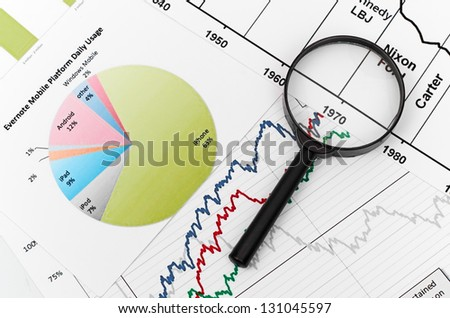 magnifying glass on graph business search - stock photo