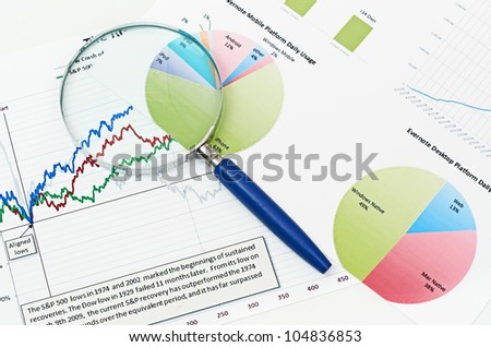 magnifying glass on graph business search background - stock photo
