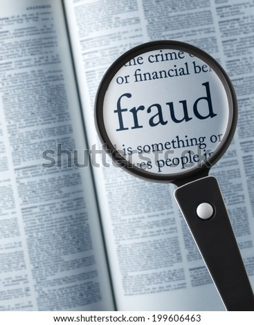 "Magnifying glass on the""fraud"" in dictionary - stock photo"