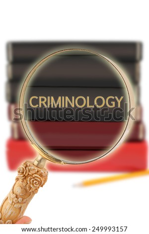 Magnifying glass or loop looking on an educational subject - Criminology - stock photo