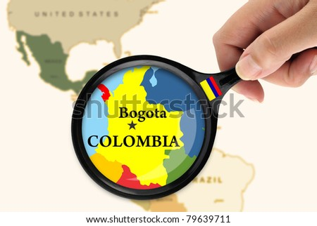 Magnifying glass over a map of Colombia - stock photo