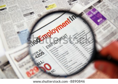 Magnifying glass over a newspaper classified section - stock photo
