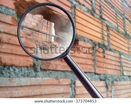 magnifying glass over brick walls cracked before electric sockets installationat house construction site  - stock photo