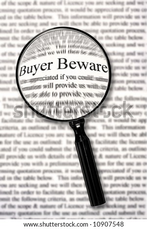 "Magnifying glass over contract document, highlighting words ""buyer beware."" - stock photo"