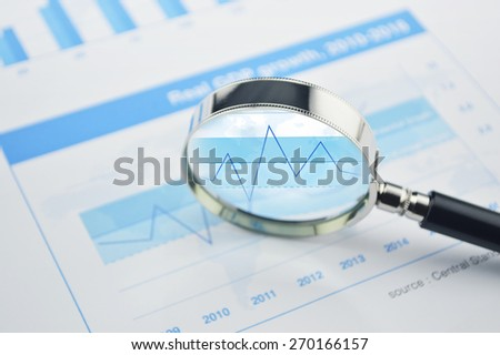 Magnifying glass over financial chart and graph business, analysis concept - stock photo