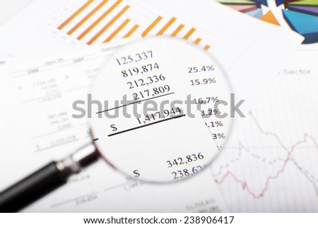 Magnifying glass over financial figures. - stock photo