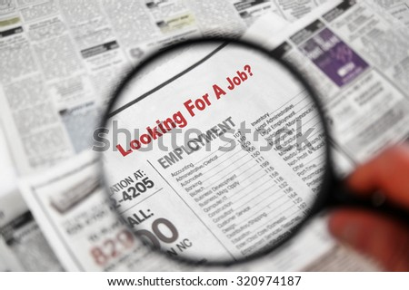Magnifying glass over Jobs section of newspaper classifieds - stock photo