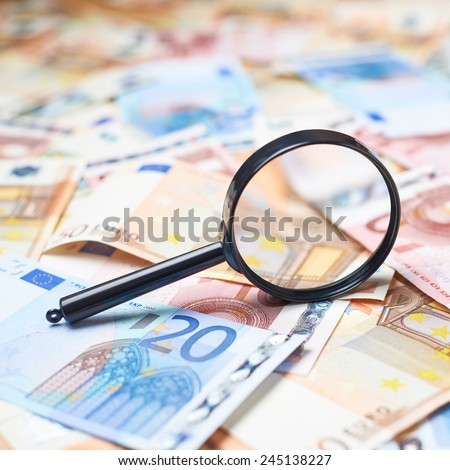 Magnifying glass over the surface covered with multiple euro bank note bills, shallow depth of field composition - stock photo