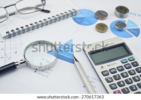 Magnifying glass, pen, glasses and calculator on financial chart and graph, accounting background - stock photo