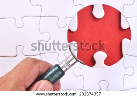 magnifying glass searching for missing puzzle pieces  - stock photo