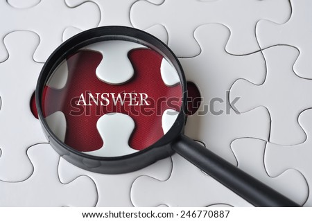 """Magnifying glass searching missing puzzle peace """"ANSWER"""" - stock photo"""