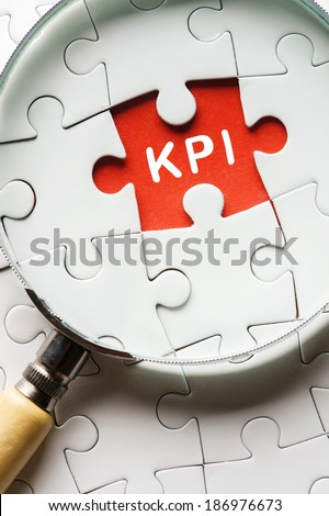 """Magnifying glass searching missing puzzle peace """"KPI"""" - stock photo"""
