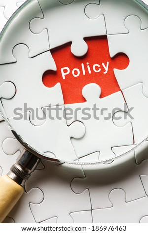 "Magnifying glass searching missing puzzle peace ""POLICY"" - stock photo"