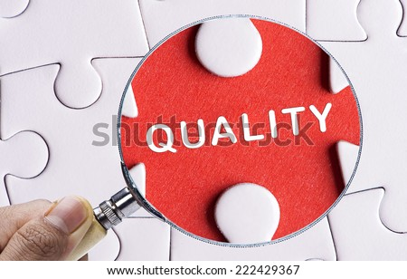 """Magnifying glass searching missing puzzle peace """"QUALITY"""" - stock photo"""