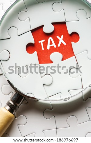 "Magnifying glass searching missing puzzle peace ""TAX"" - stock photo"